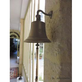 Cloche en laiton poli sur mur en pierre